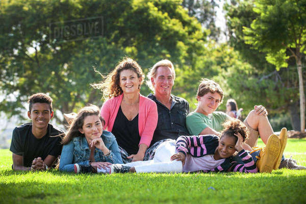 Portrait of smiling family on grass in park Royalty-free stock photo