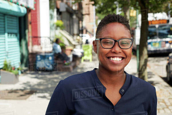 Woman wearing eyeglasses smiling on city sidewalk Royalty-free stock photo