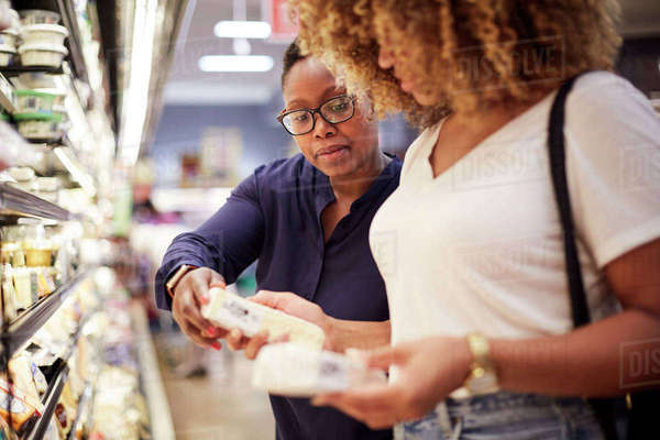 Women examining cheese in grocery store Royalty-free stock photo