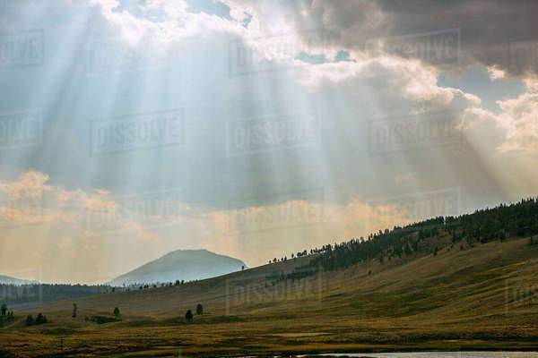 Sunbeams shining through clouds over rolling rural landscape Royalty-free stock photo