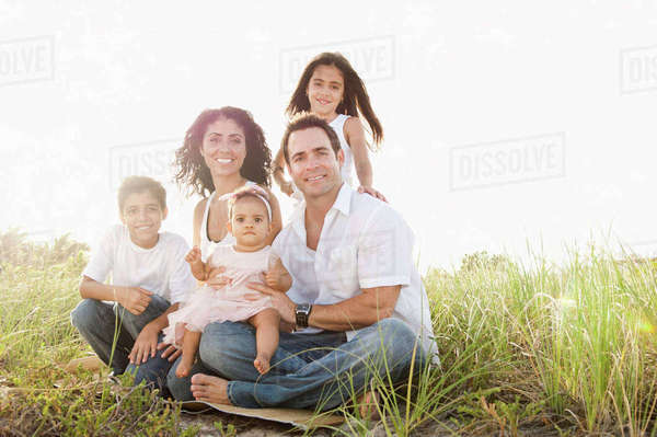Portrait of Mixed Race family sitting in grass Royalty-free stock photo