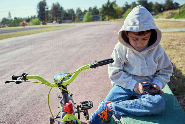 Hispanic boy sitting near bicycle texting on cell phone Royalty-free stock photo