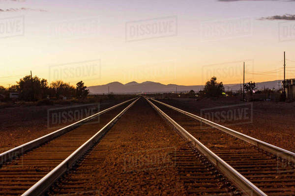 Railroad tracks in mountain landscape at sunset Royalty-free stock photo