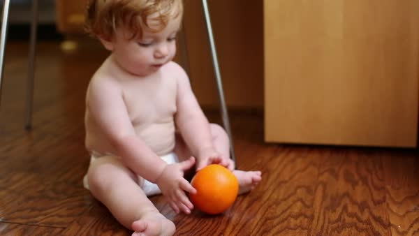 Caucasian baby boy sitting on floor playing with orange Royalty-free stock video