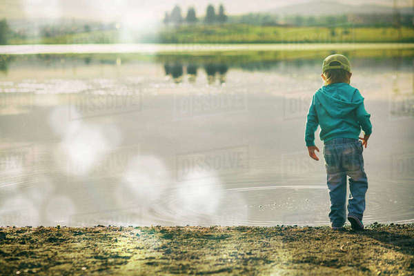 Boy watching ripples in lake Royalty-free stock photo