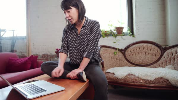 Asian woman sitting on coffee table video chatting with laptop Royalty-free stock video