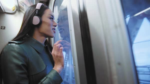 Thai transgender woman listening to headphones on subway train Royalty-free stock video