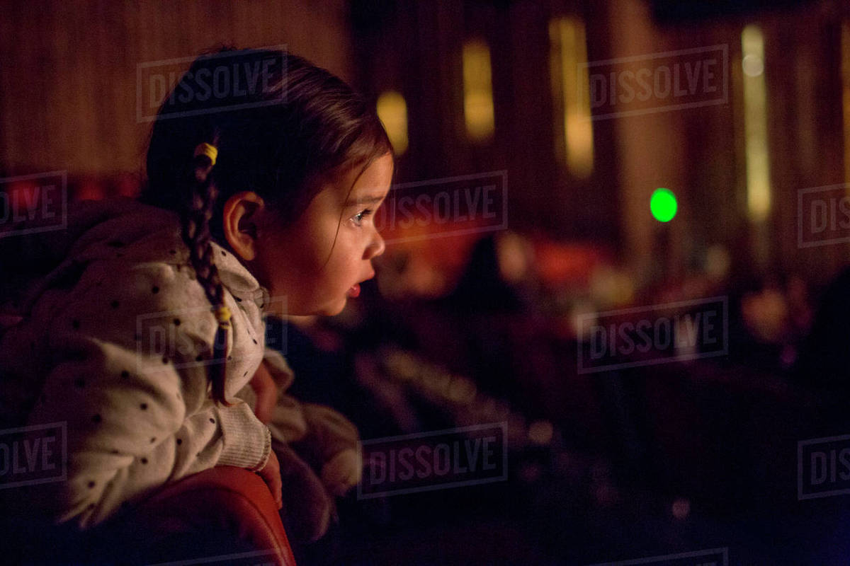Mixed Race girl leaning on chair watching movie in theater Royalty-free stock photo