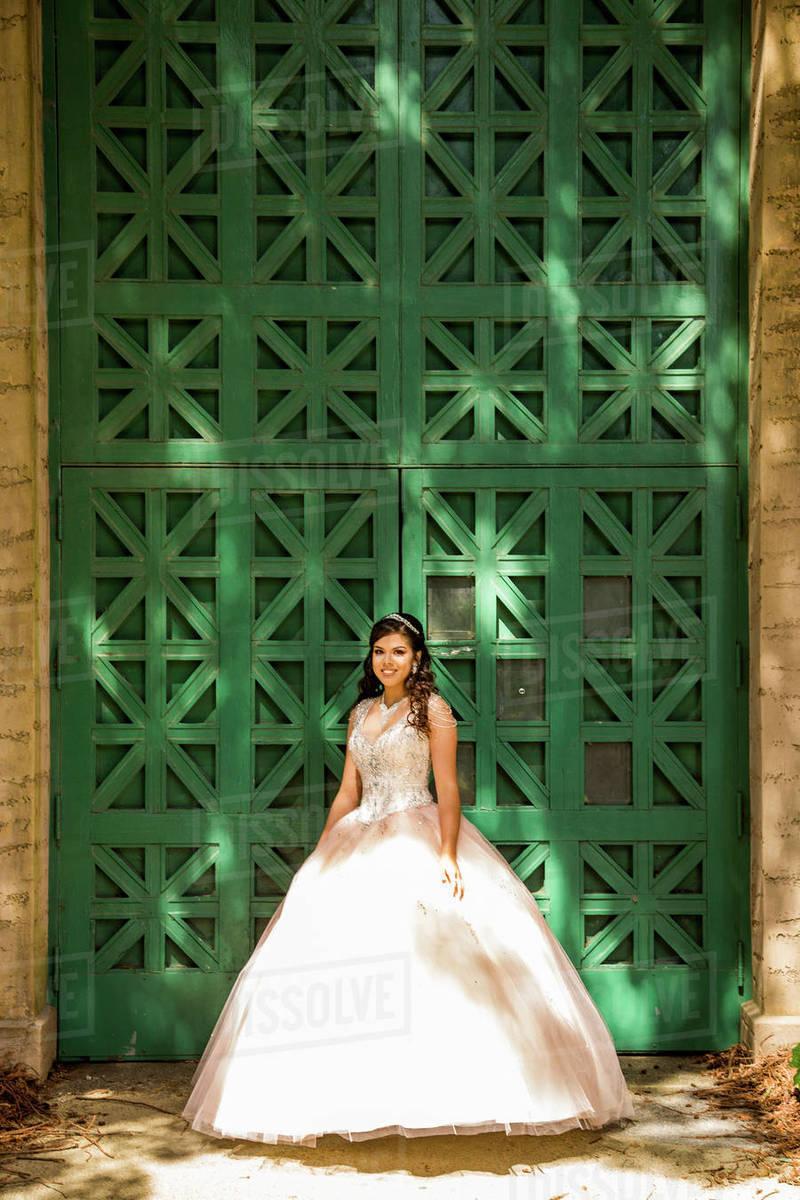 faf4c2063a29 Smiling Hispanic girl wearing gown near green wall - Stock Photo ...