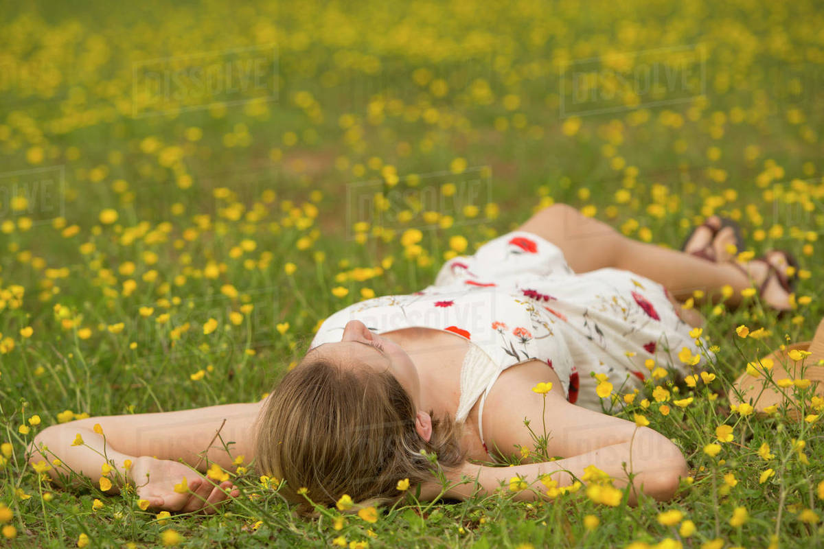 Caucasian teenage girl laying in field of flowers - Stock ...