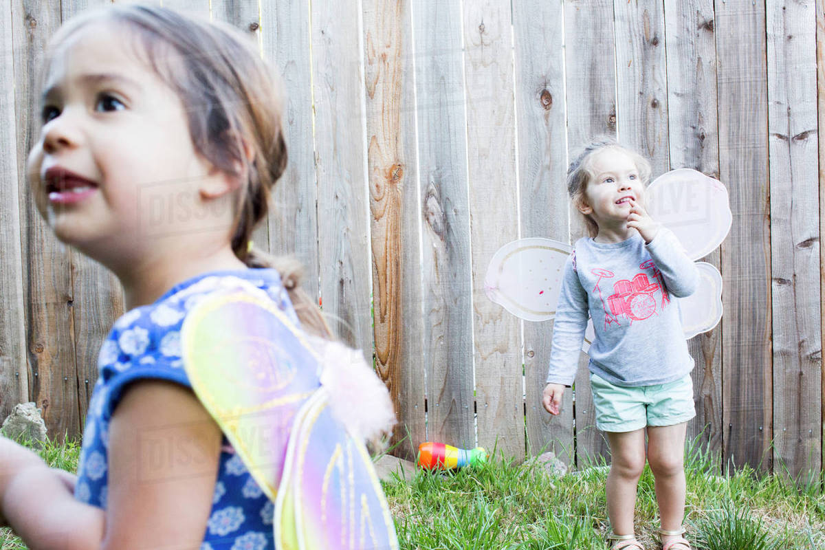 Curious girls wearing fairy wings in backyard Royalty-free stock photo