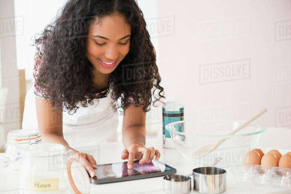 Mixed race woman using digital tablet while cooking Royalty-free stock photo