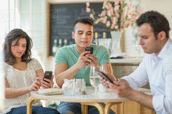 Hispanic friends using cell phones in cafe Royalty-free stock photo
