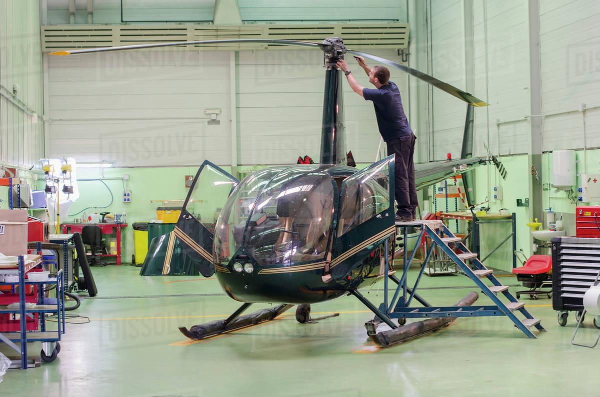 Hispanic mechanic working on helicopter in hangar Royalty-free stock photo