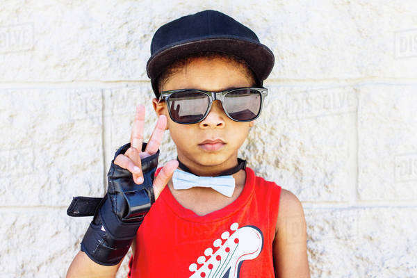 African American boy wearing bow tie, wrist brace, sunglasses and baseball cap Royalty-free stock photo