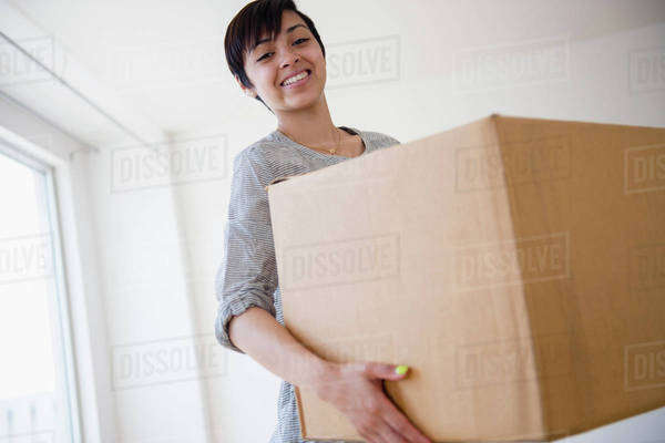 Smiling mixed race woman carrying cardboard box Royalty-free stock photo