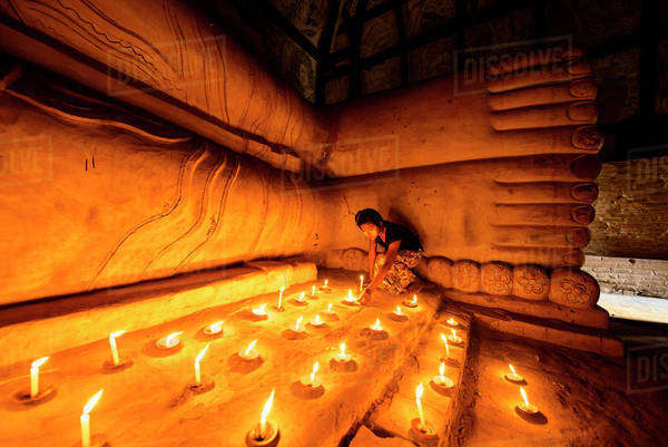 Asian girl lighting prayer candles in Buddhist temple Royalty-free stock photo