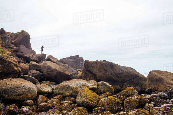 Person standing on mossy rocks on beach Royalty-free stock photo