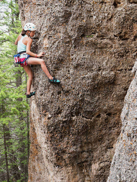 Mixed race girl climbing steep cliff Royalty-free stock photo