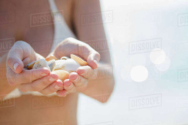 Close up of Caucasian woman holding seashells at beach Royalty-free stock photo