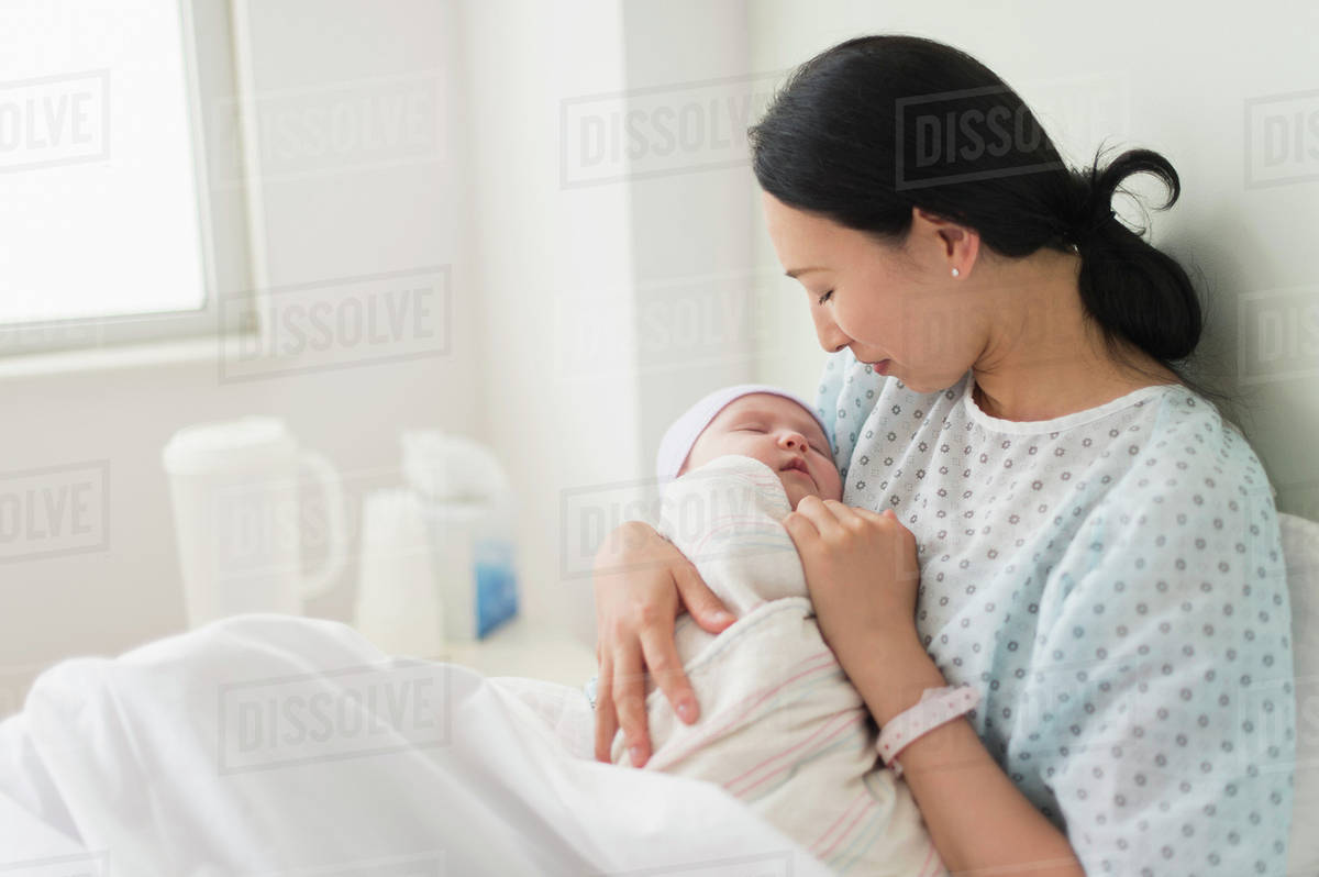 asian mother holding newborn baby in hospital bed stock