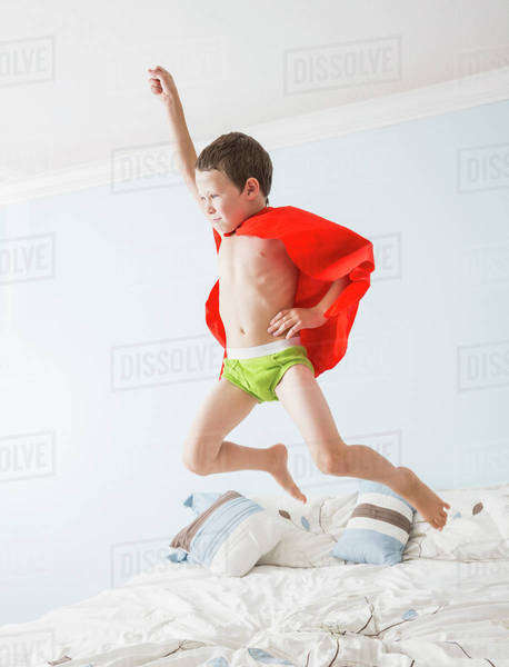Caucasian boy playing superhero on bed Royalty-free stock photo