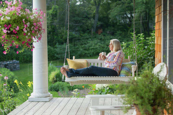 Older Caucasian woman drinking cup of coffee on porch swing Royalty-free stock photo
