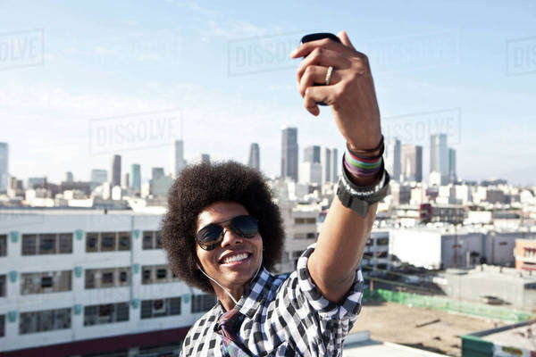 African American man taking cell phone picture from urban rooftop Royalty-free stock photo