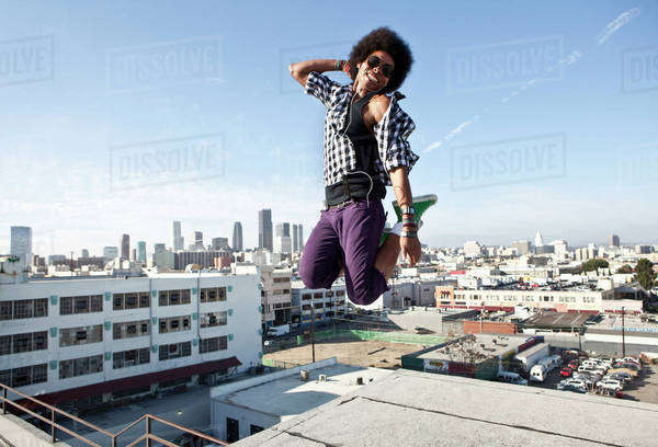 African American man jumping for joy on urban rooftop Royalty-free stock photo