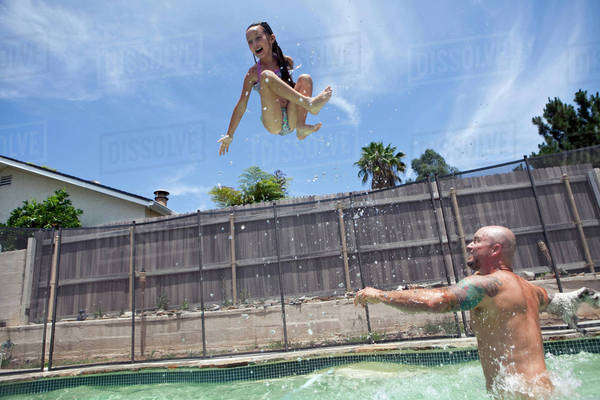 Caucasian father throwing daughter in backyard swimming pool Royalty-free stock photo