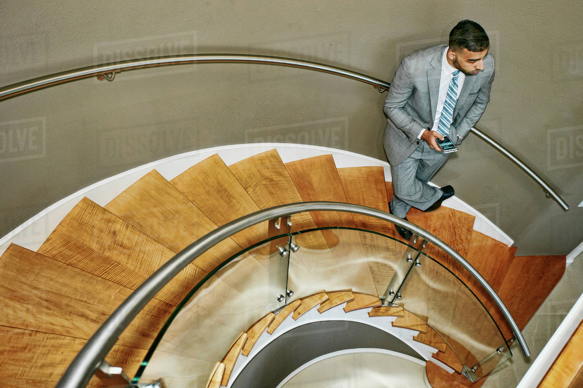 High Angle View Of Middle Eastern Businessman Standing On Spiral Staircase