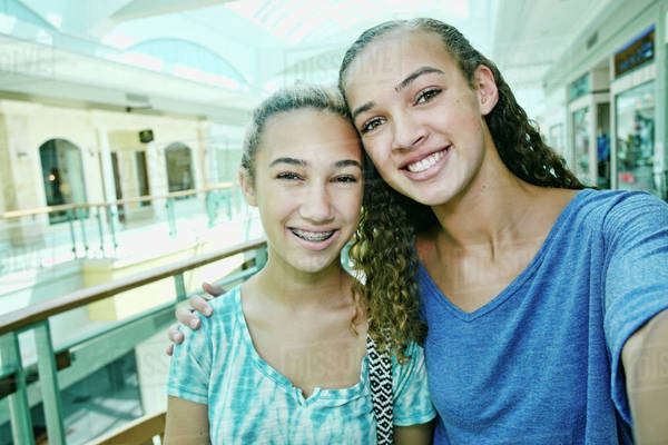 Mixed race teenage girls smiling at shopping mall Royalty-free stock photo