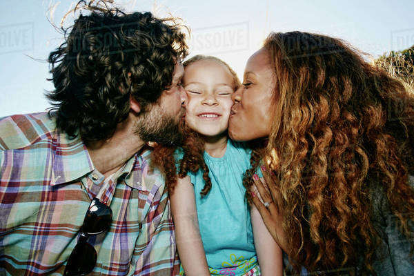 Parents kissing cheeks of daughter outdoors Royalty-free stock photo