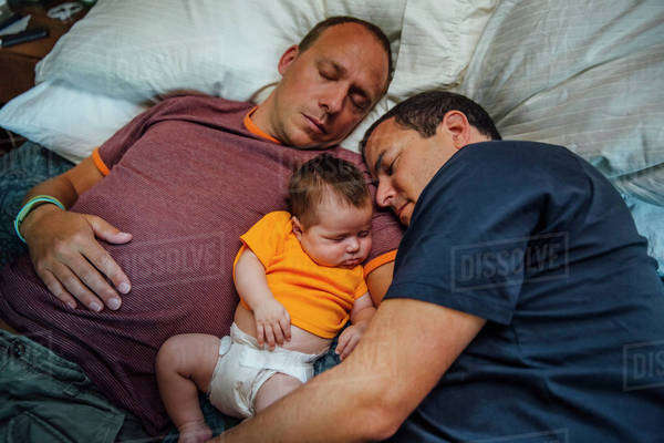 Caucasian fathers and baby boy sleeping on bed Royalty-free stock photo