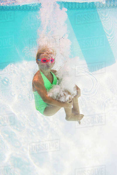 Caucasian girl swimming underwater in pool Royalty-free stock photo
