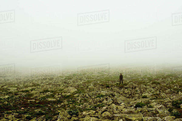 Caucasian hiker walking in rocky field Royalty-free stock photo