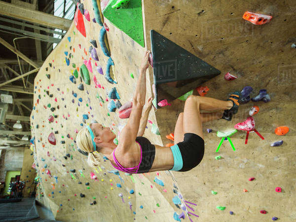 Caucasian woman climbing indoor rock wall Royalty-free stock photo