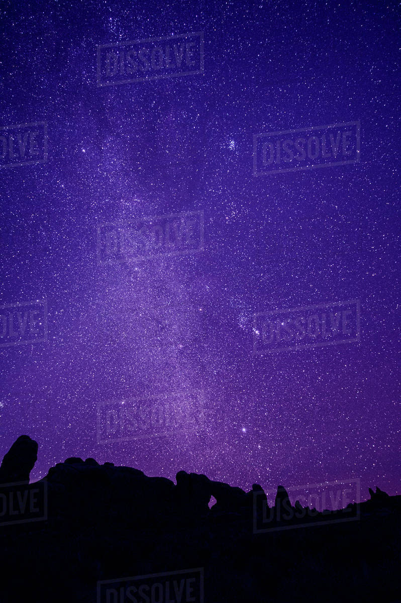 Silhouette of rock formations under starry night sky stock photo