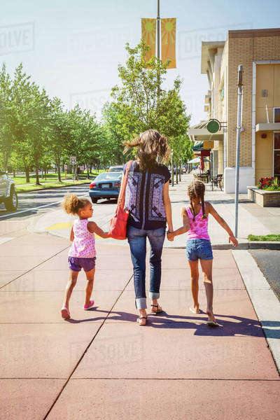 Mother and daughters holding hands on neighborhood sidewalk Royalty-free stock photo