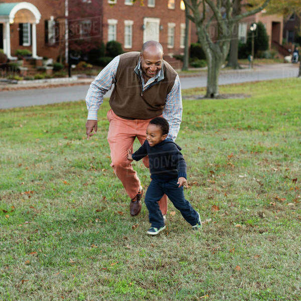 African American father and son playing in park Royalty-free stock photo