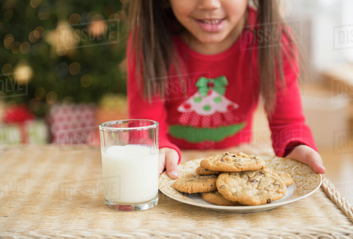 Hispanic Girl Setting Out Milk And Cookies For Santa Stock Photo