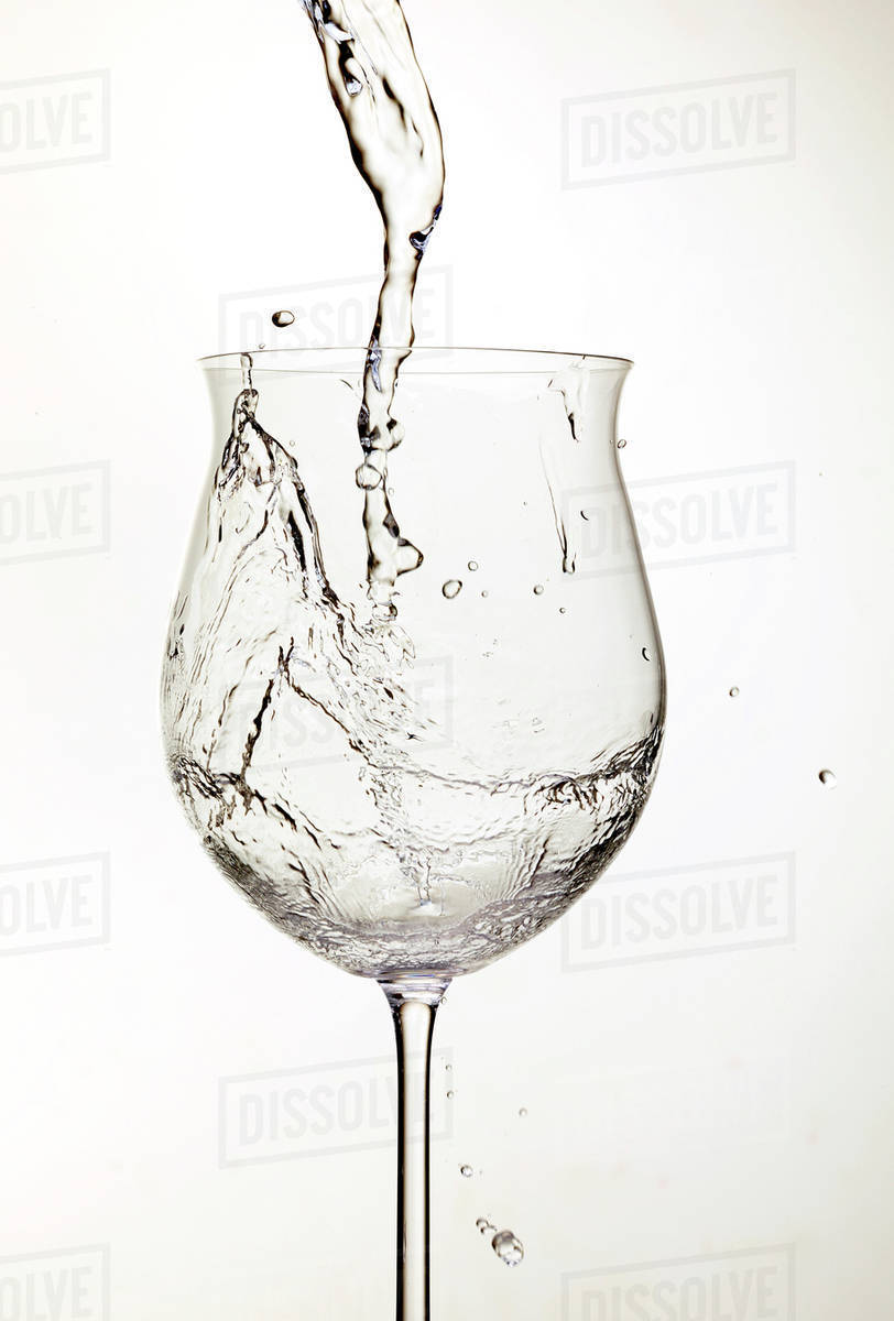 Water Pouring Into Wine Glass Stock Photo