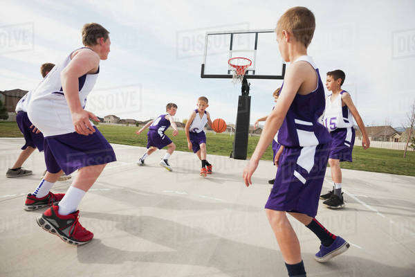 Caucasian boys playing basketball on court Royalty-free stock photo