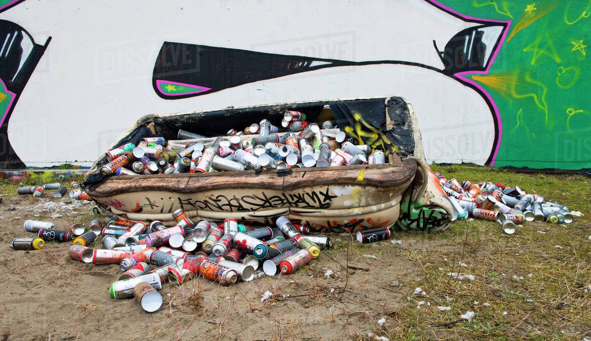 Dumpster filled with spray paint cans on city street with graffiti stock  photo