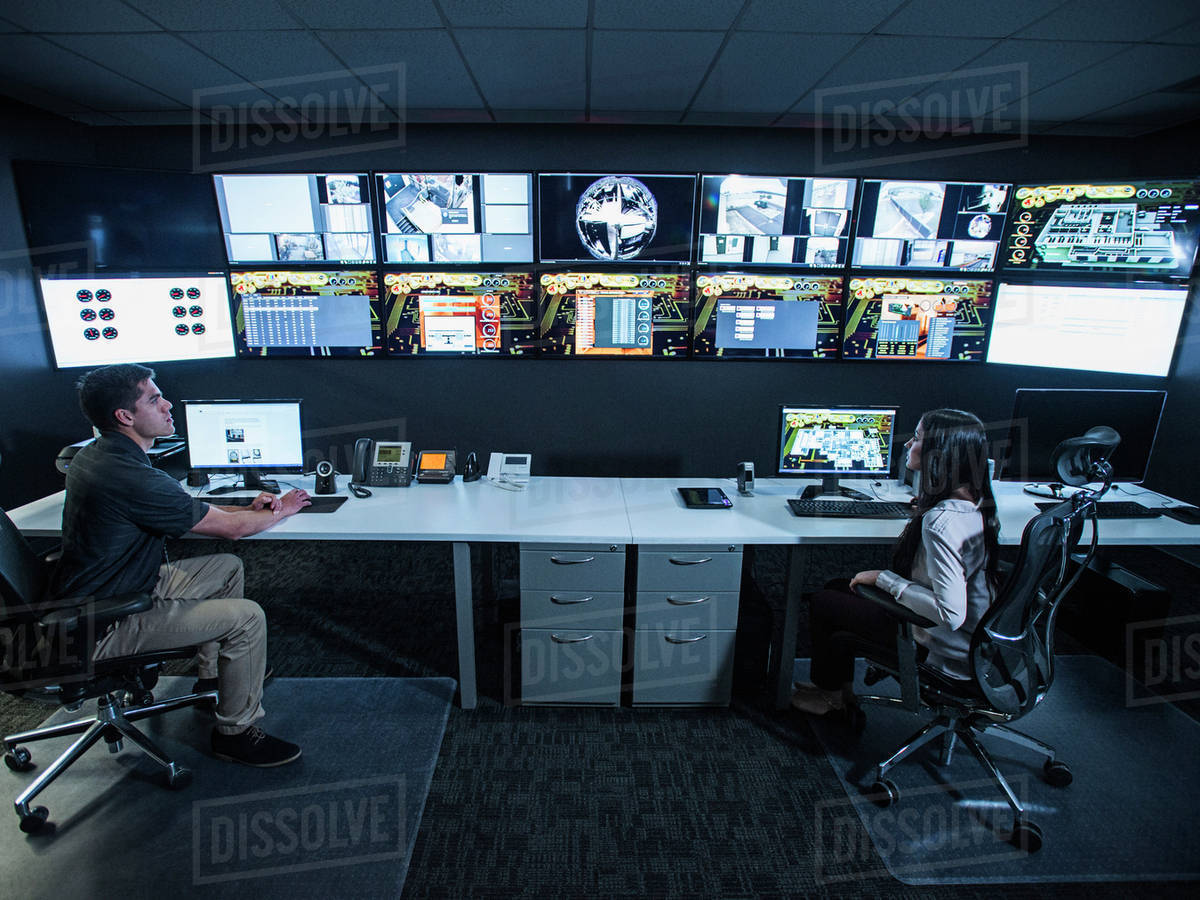 Security Guards Watching Monitors In Control Room Stock