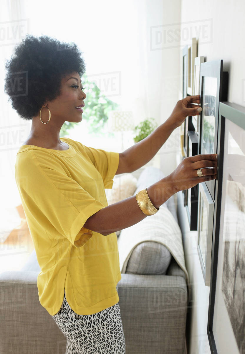 African American woman hanging pictures on living room wall - Stock ...