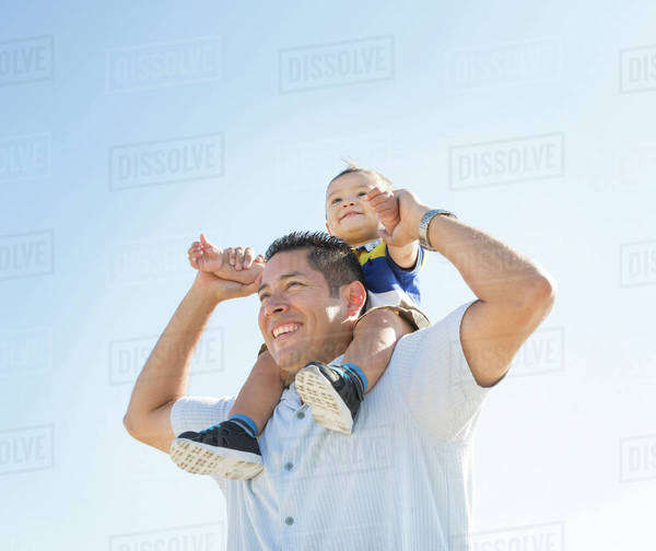 Low angle view of Hispanic father carrying son on shoulders Royalty-free stock photo