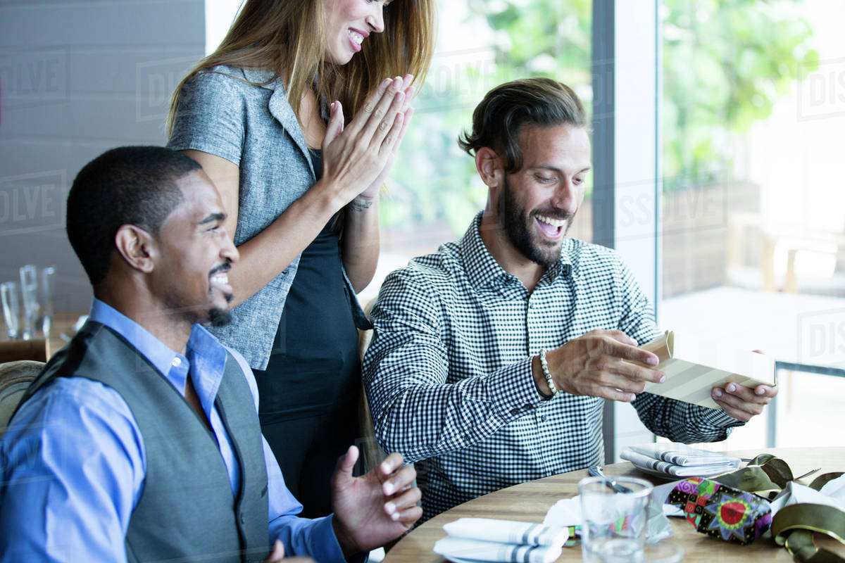 Businessman Opening Gifts At Birthday Lunch