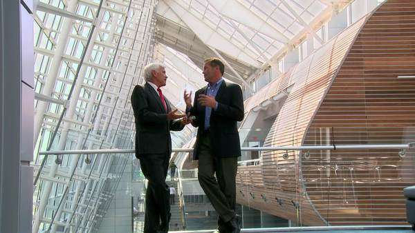 Businessmen talking and shaking hands in atrium Royalty-free stock video