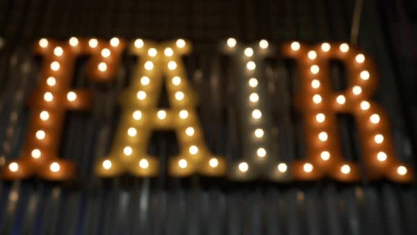 Hand-held shot of fair word made of light bulbs Royalty-free stock video